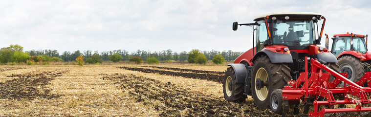 Fototapete - Several powerful tractors work in the field