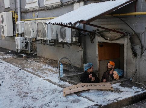 Restaurant employees smoke near a service entrance in central Kiev