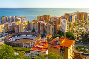 Aerial cityscape of Malaga center in Spain at sunset. View of sea, bullring, harbor and other tourist attractions. Landscape of Costa del Sol.