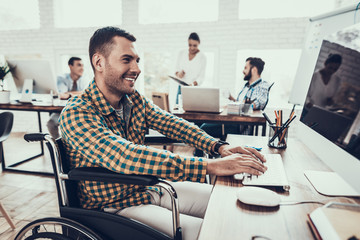 Man on Wheelchair Working on Computer in Office.
