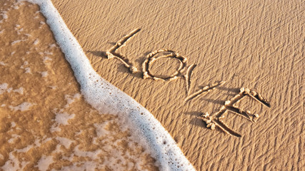 inscription LOVE on the sand of the beach. wave on the shore