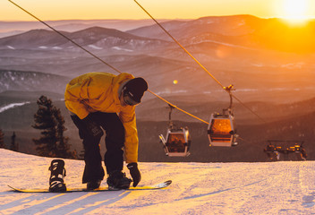 the guy comes on a snowboard at sunset