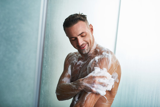 Handsome young man washing himself with shower gel