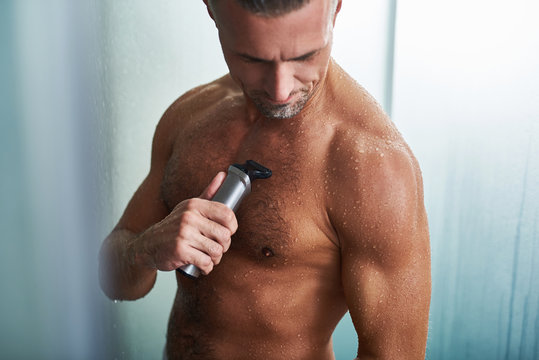 Young man with muscular wet body shaving chest after shower