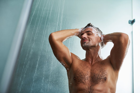 Handsome young man with beautiful body washing his hair