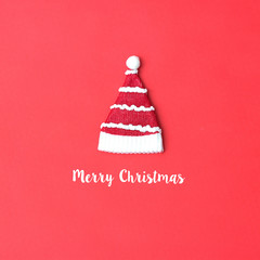 Santa Claus hat flat lay on red background with word merry christmas. Minimal style. Holiday concept.
