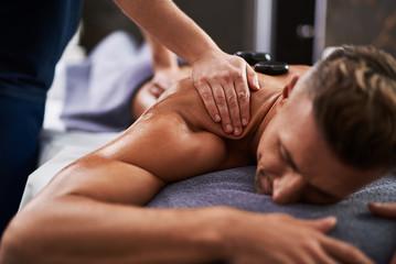 Masseur hands massaging client shoulder while he lying on massage table