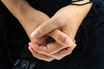 Woman's hands praying on Black scarf background, Close up & Macro shot, Selective focus, Asian body skin part, Symbol, Gesturing, Body Language concept