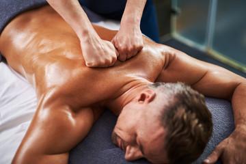 Professional masseur massaging client back at spa salon