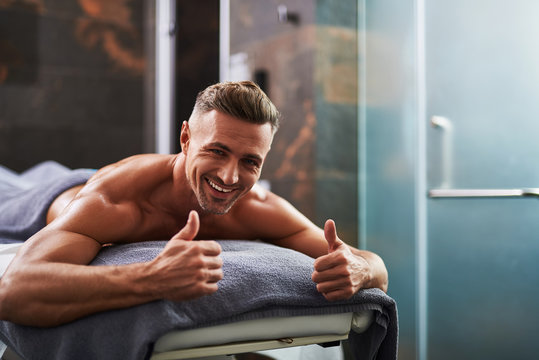 Handsome young man doing thumbs up sign while lying on massage table