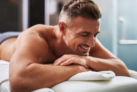 Handsome young man with closed eyes lying on massage table
