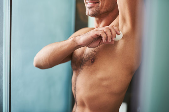 Young man with perfect body applying antiperspirant on armpit