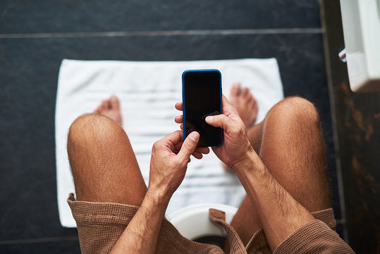 Young gentleman using mobile phone while sitting on toilet bowl