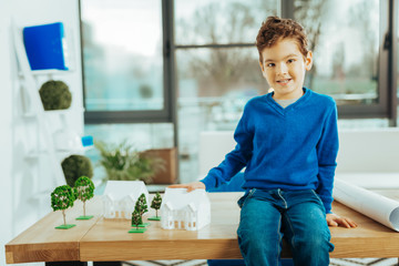 Cheerful boy sitting on the table and playing with miniature houses