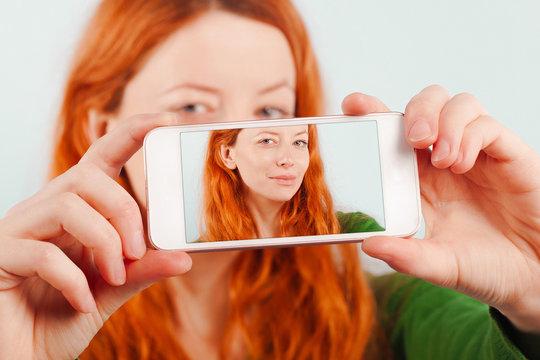 Redhead girl making selfie using phone.