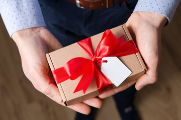 Close up man holding Valentine's day gift in hands, red ribbon, gift tag,romantic surprise