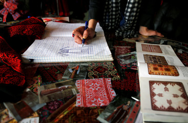 Palestinian woman draws a traditional dress design at a sewing factory in Ramallah, in the Israeli-occupied West Bank