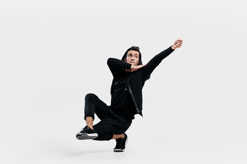 Dark-haired stylish dancer dressed in a black clothes makes stylized movements of street dance. He is sitting on one leg and put his hand up