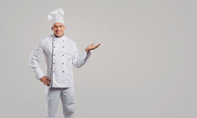 Chef in a white uniform makes a gesture.