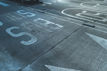 Rough gray surface of street road pavement with marking of bus stop, Mexico city