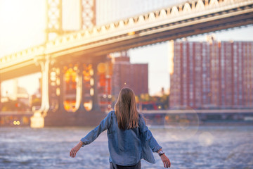 Woman standing near the river in New York, Brooklyn Bridge. - Image