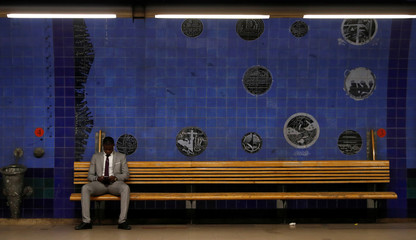 A man waits for the train at a subway station in Lisbon