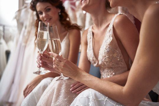 Close up of happy young brides with champagne