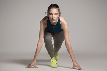 Young active sprinter woman dressed in sportswear prepare for the start. Gray background.