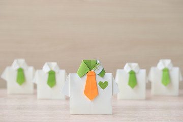 Leadership and teamwork concept, Origami yellow shirt with tie and leading among small yellow shirt on wooder background