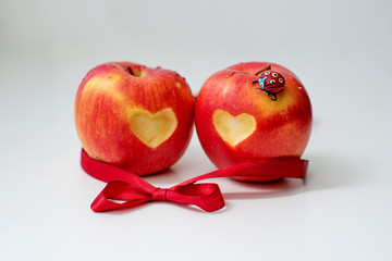 Love of two apples concept with a neatly incised heart in the skin of a ripe red apple on white table