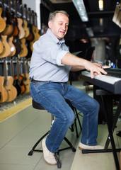 Smiling musician is playing on modern keyboard