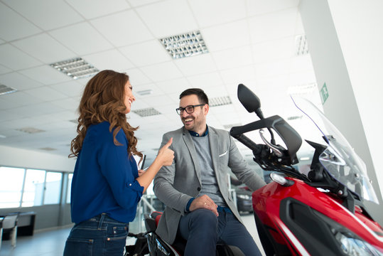 Attractive young man in dealership showroom buying new motorcycle.