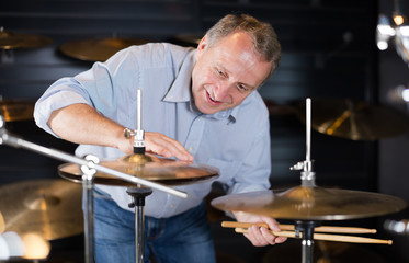 Adult male musician is playing on modern drum kit