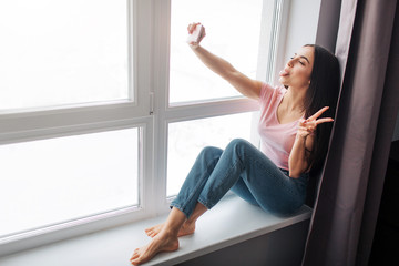Cheerful young woman take selfie at window. She smile and pose. Model show piece sign with fingers.