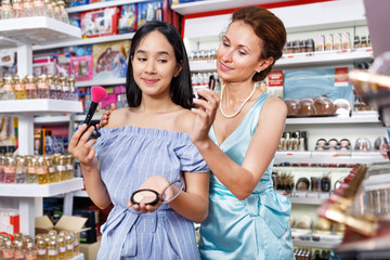 Girl and mother testing face powder at cosmetics shop