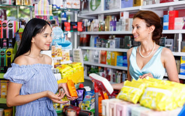 Smiling saleswoman helping to girl client  with purchases in salon