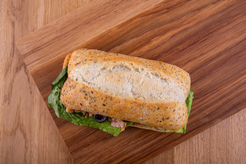 Sandwich from gray bread with fish and lettuce leaves
