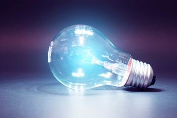 Colourful light bulb putting on the black ground with light blue flare on it.