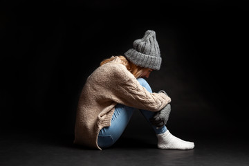 The girl is sitting alone on the floor on a black background of emptiness having embraced her legs with her hands and dropping her face on her knees crying faced a problem.