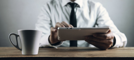 Coffee cup on table. Businessman using white digital tablet.