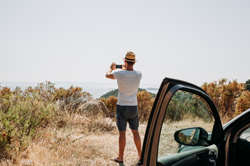 Young man taking a picture of the seaside out of his car