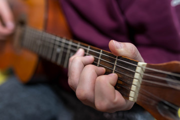 Young unidentifiable musician playing on the guitar shallow depth of field.