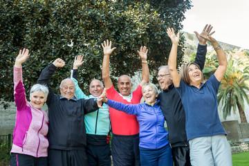 Gruppo di anziani felici che sollevano le braccia al cielo e ridono