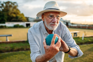 Elderly man playing a game of boules