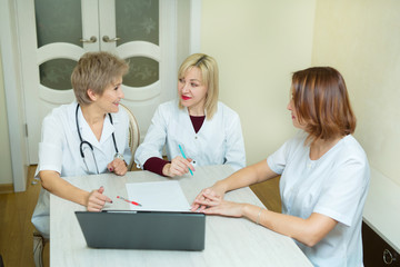 three women doctor in white coats sit at the table in the clinic in the office with a laptop