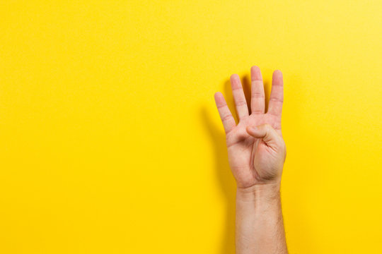Man hand showing four fingers on yellow background. Number two symbol