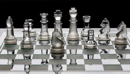 Assortment of glass chess pieces on a board with black and white shade