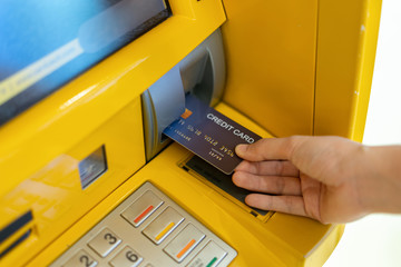 Hand inserting ATM or credit card into bank machine to withdraw cash money