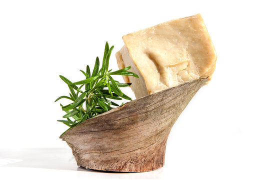 Pieces of handmade olive and herbs soap with rosemary on wood isolated on white.