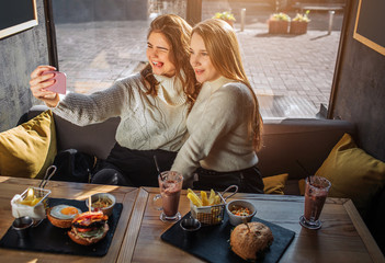 Cheerful young women sit at table inside in cafe and take selfie. They sit together and pose. Models smile. They have food and drinks at table.